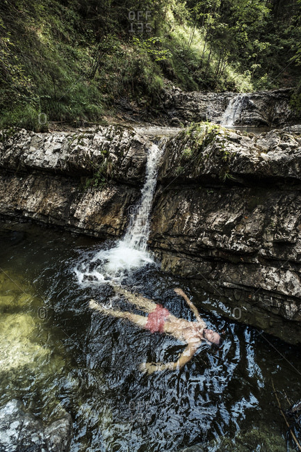 Germany- Upper Bavaria- Bavarian Prealps- lake Walchen- young man is swimming in a plunge pool