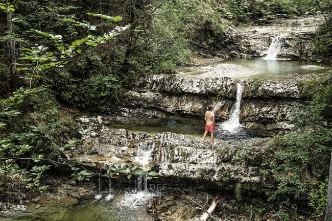 Germany- Upper Bavaria- Bavarian Prealps- lake Walchen- young man is standing in a torrent