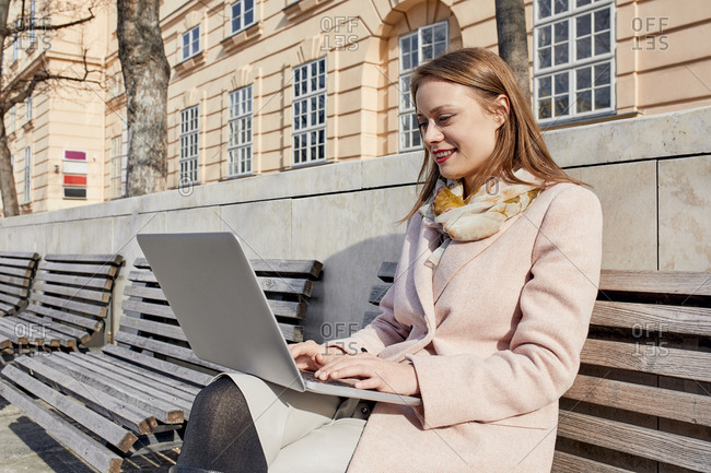 Austria- Vienna- smiling young woman sitting on bench at Museums Quartier using laptop