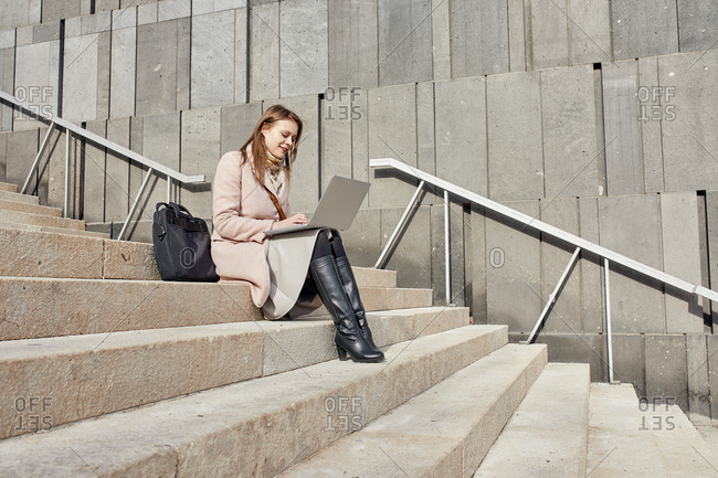 Austria- Vienna- smiling young woman sitting on stairs at Museums Quartier using laptop