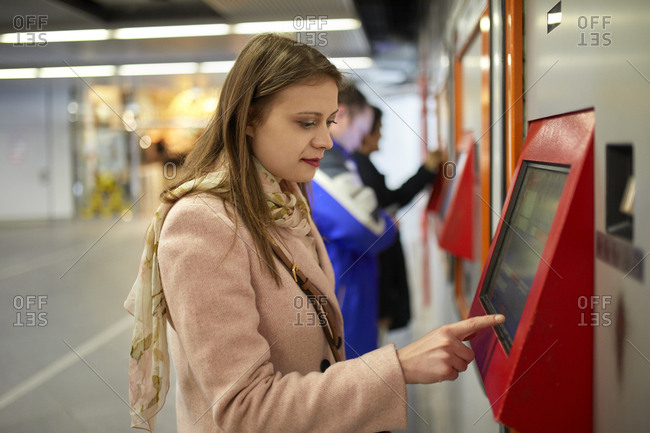 Austria- Vienna- young woman buying ticket from automated machine at station