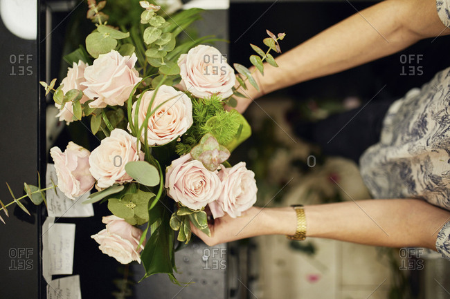 Close-up of florist arranging flowers in flower shop
