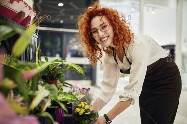 Portrait of smiling florist arranging flowers in flower shop