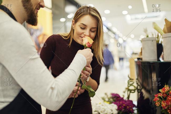 Florist letting customer smell at flower in flower shop