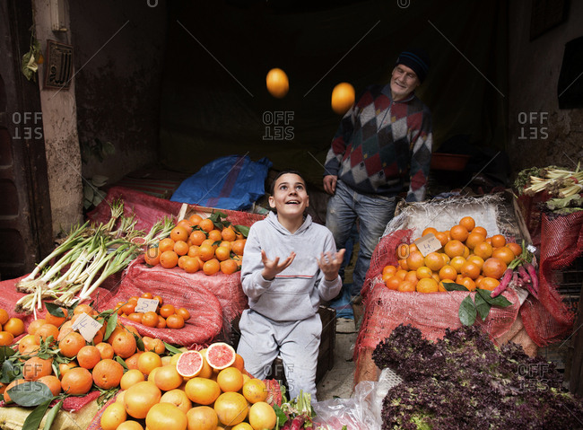 Fes El Bali, Morocco - April 6, 2019: Boy and grandfather selling fruit and oranges at the Medina of Fez market