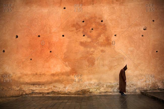 Man walking by large tan colored wall near main market wearing traditional Djellba robe, Rabat, Morocco
