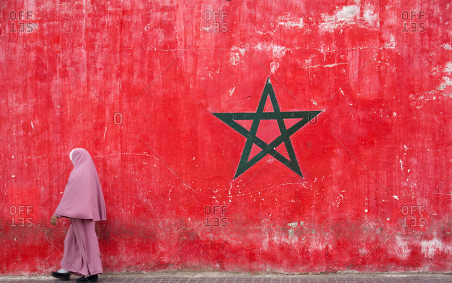Muslim woman walking by wall with painting of national Moroccan flag, Casablanca, Morocco