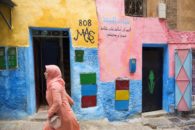 Fes, Morocco - April 6, 2019: Woman walking by colorful buildings on a backstreet in Fes