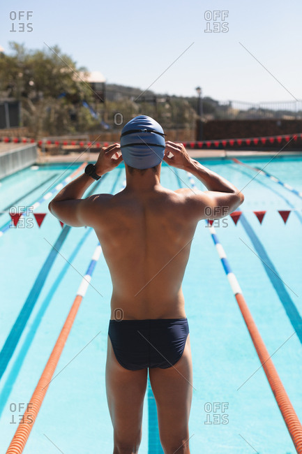 Young male swimmer standing at swimming pool