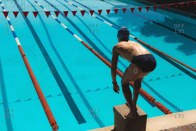 Young male swimmer standing on starting block