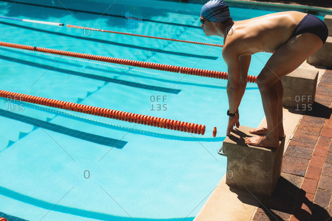 Young male swimmer standing on starting block at swimming pool