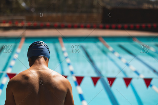 Rear view of young male swimmer standing at swimming pool