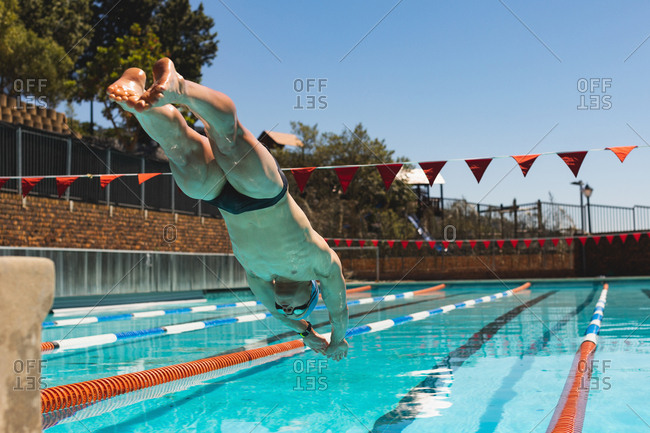 Young Caucasian male swimmer jumping into water of a swimming pool