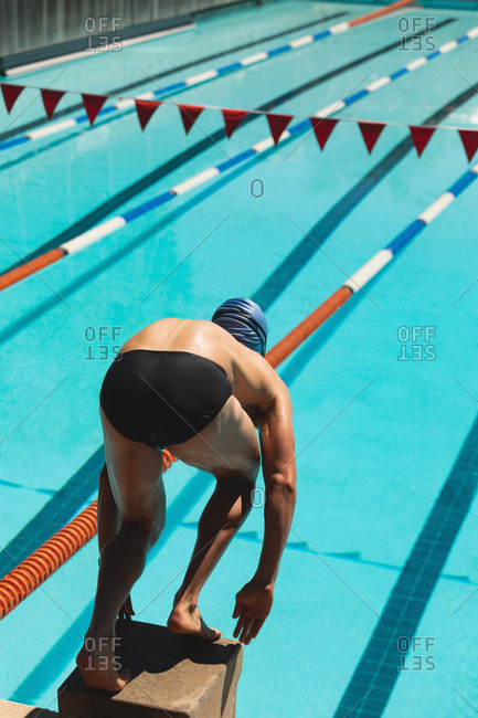 Male swimmer standing on starting block in starting position