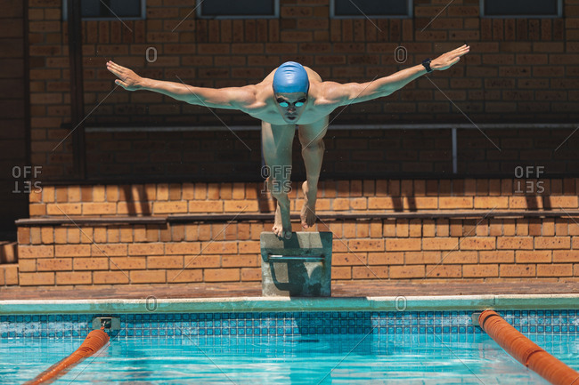 Young Caucasian male swimmer with arms stretched out jumping into swimming pool