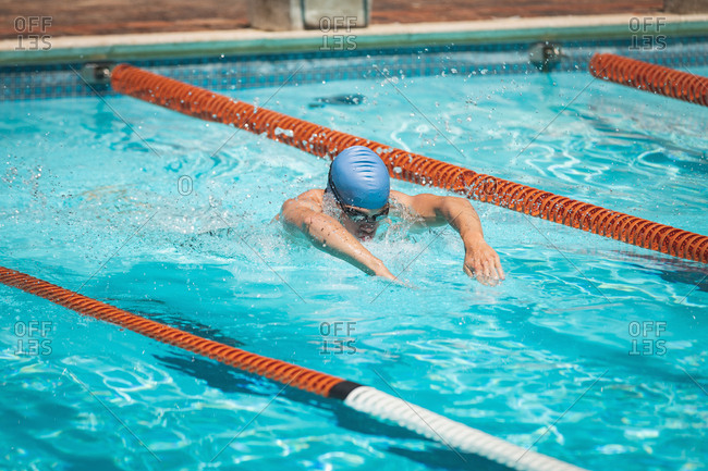 Young Caucasian male swimmer swimming butterfly stroke