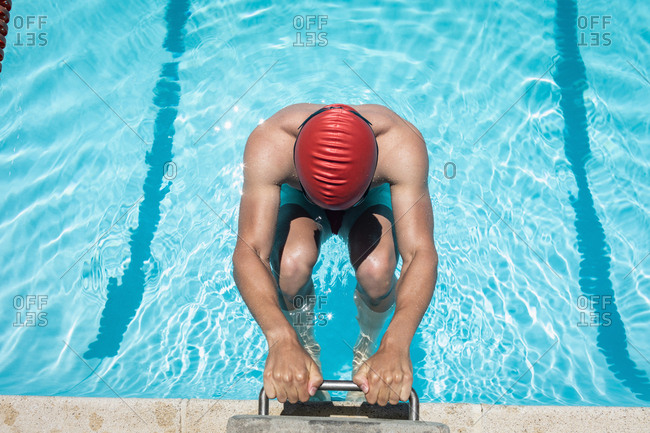Young Caucasian male swimmer holding starting block in swimming pool