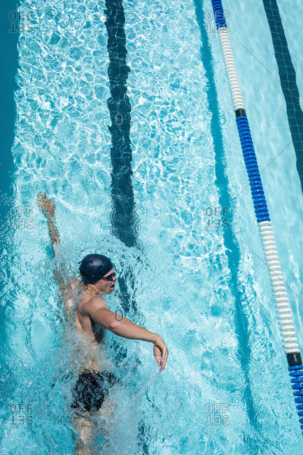 Young swimmer swimming freestyle in swimming pool