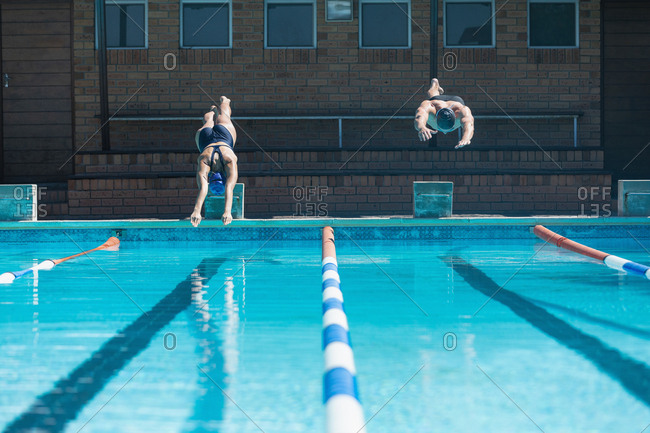 Young swimmers jumping into water at swimming pool