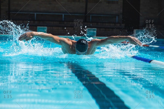 Young man swimmer with swim goggle swimming at swimming pool