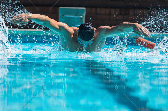 Young male swimmer with swim goggle swimming at swimming pool