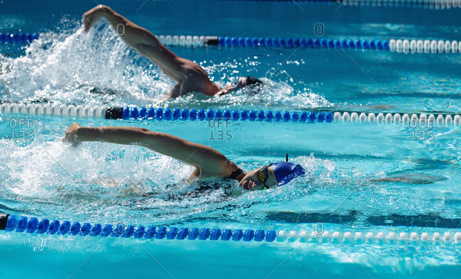 Two female swimmer swimming freestyle in swimming pool