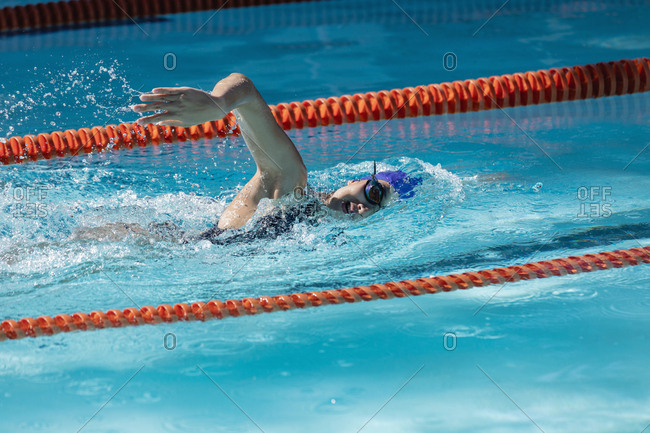 Female swimmer swimming freestyle in swimming pool