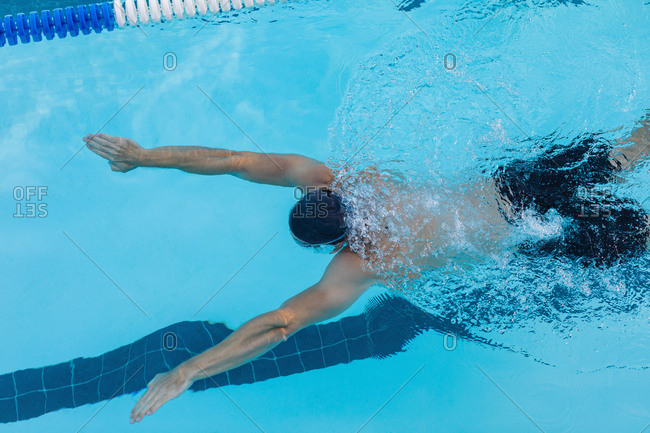 Male swimmer swimming breaststroke in swimming pool