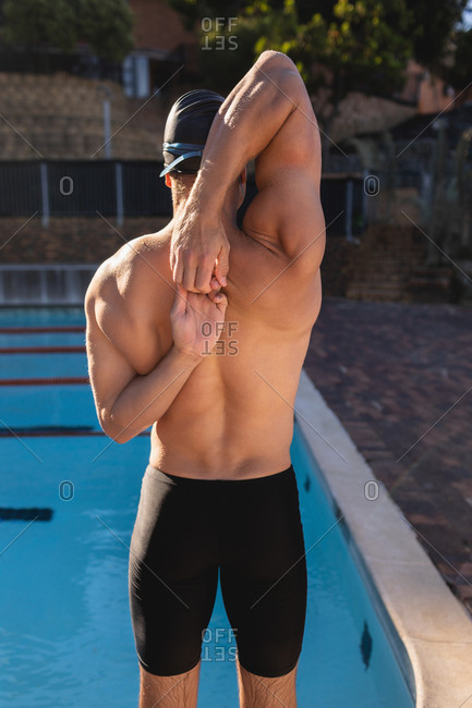 Male swimmer stretching next to the swimming pool