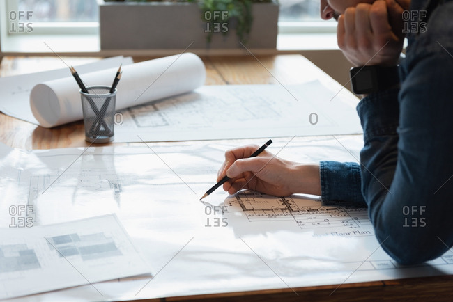 Businessman standing and working over blueprint at office conference