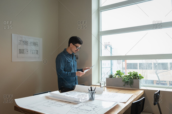 Businessman standing and looking blueprint at office meeting room