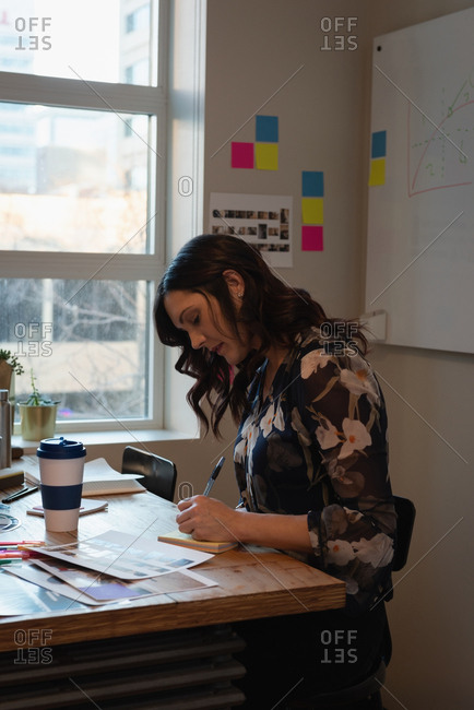 Businesswoman sitting and writing at notepad in office