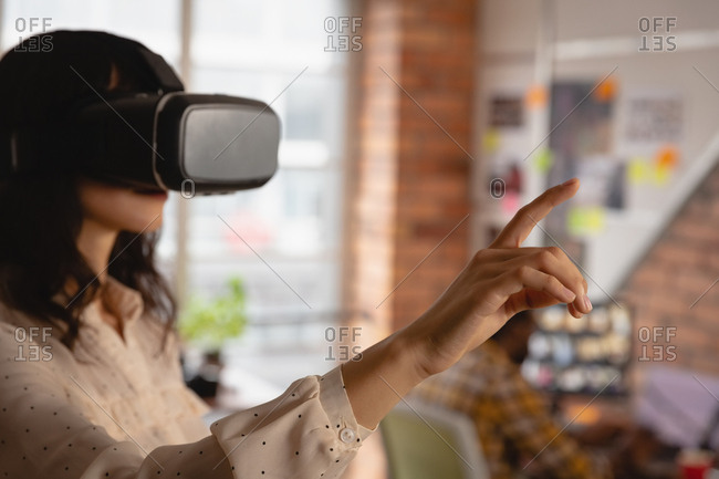 Businesswoman using virtual reality headset in office