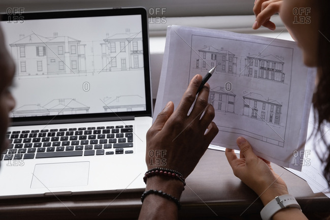 Business people discussing over blueprint in office at desk