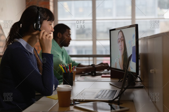 Businesswoman making video call to business partner in office at desk