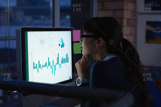 Businesswoman working over graph project in office at desk