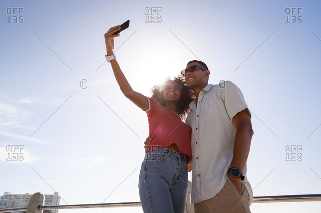 Couple standing and talking selfie at beach