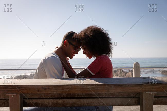 Couple in romantic mood sitting on wooden plank near sea side