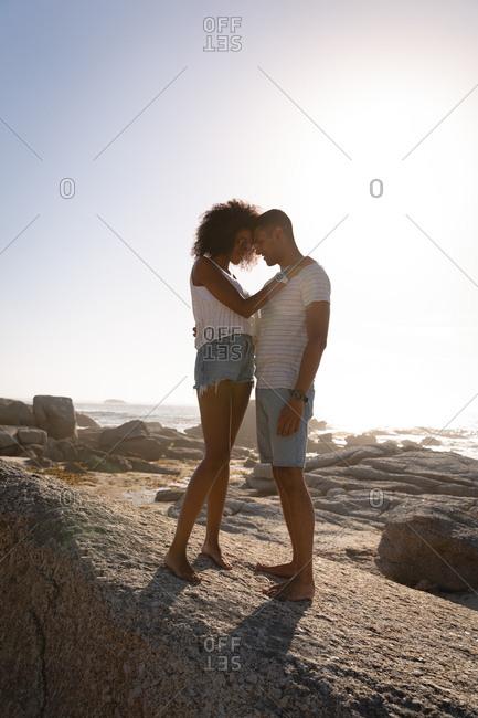 Couple in romantic mood standing on rock near sea side