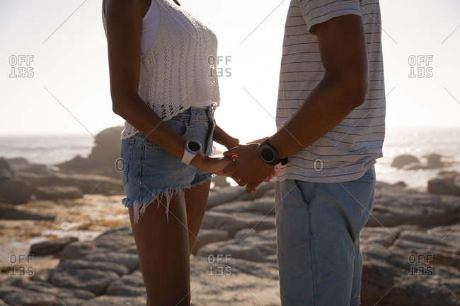 Couple holding hand in hand while standing near sea side