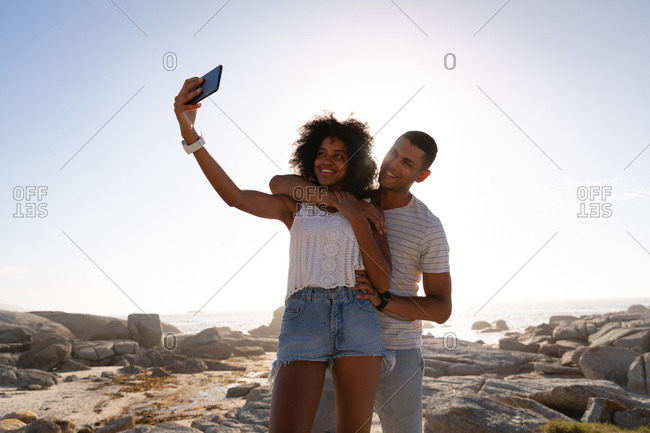 Couple standing and taking selfie near sea side