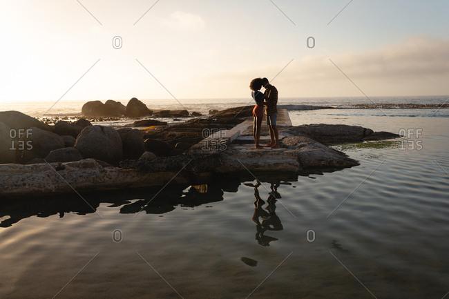 Couple standing in romantic mood near sea side on rock