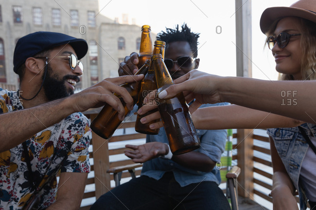 Group of friends toasting with beer bottles at home in balcony