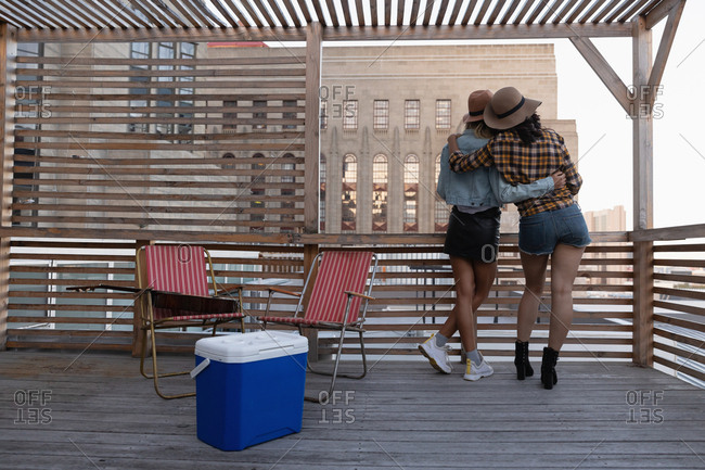 Female friends standing with arm around in balcony at home