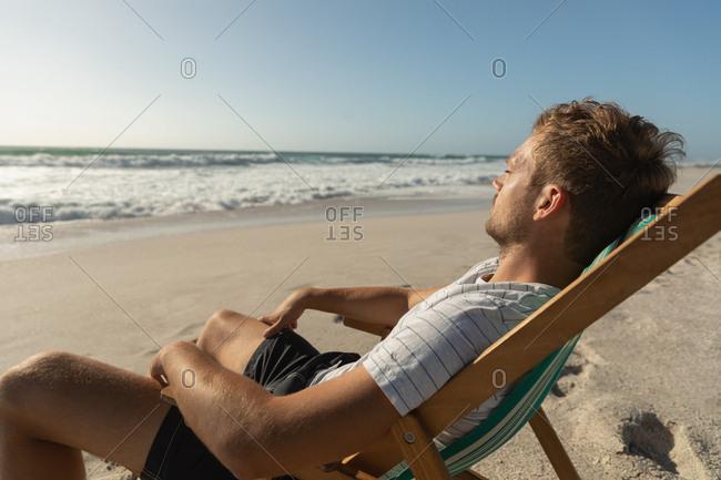 Caucasian man relaxing on sun lounger at beach
