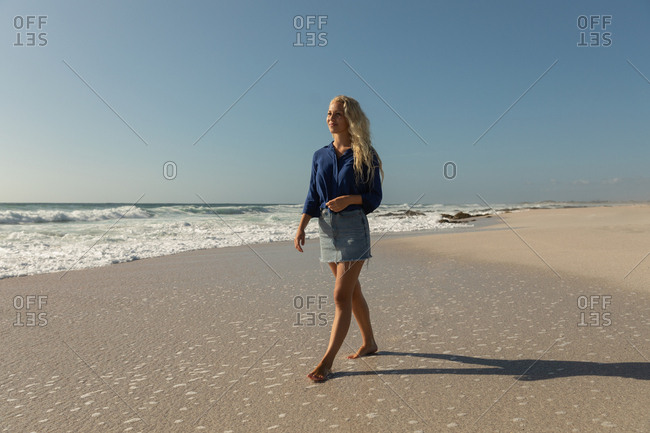 Beautiful blonde Caucasian woman walking at beach on a sunny day