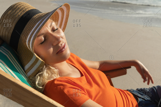 Young Caucasian woman relaxing on sun lounger at beach