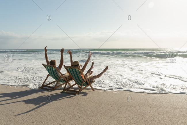 Young Caucasian couple enjoying on sun lounger at beach on a sunny day