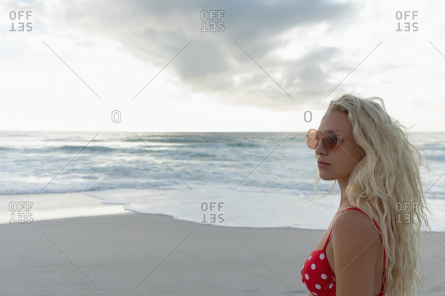 Beautiful blonde Caucasian woman standing at beach on a sunny day