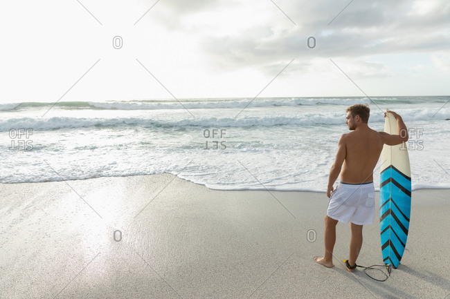 Blonde Caucasian male surfer with a surfboard standing at beach on a sunny day